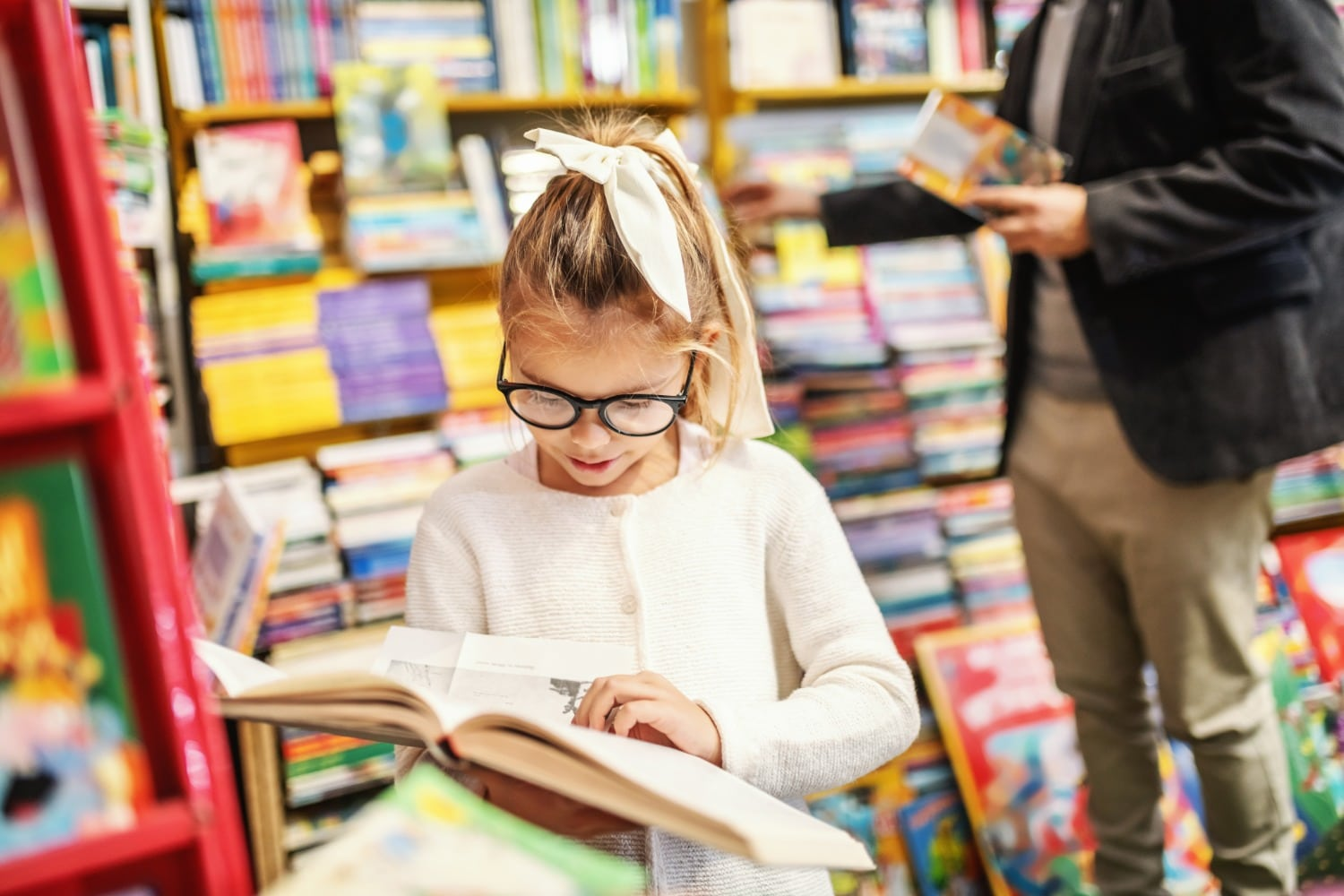 Young Girl Reading Book in Bookstore