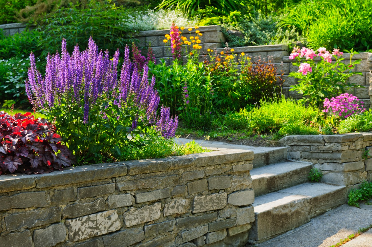 Flowers in garden with stone stairs and stone planters