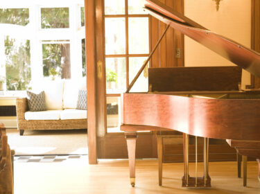 A wooden grand piano sits in a sunny room with a couch and sunroom in the background