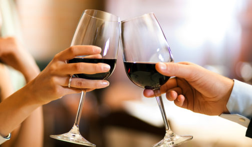 Two hands holding wine glasses filled with red wine cheer.
