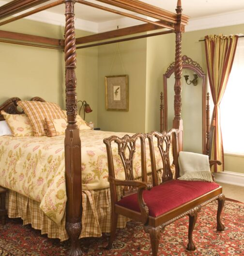 An elegant four post bed rests in a room with oriental rugs, antique furnishings, a large window, and light green walls.