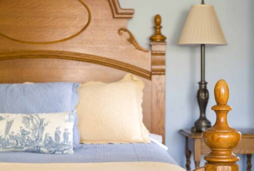 A wooden bedframe hosts a queen bed with blue and white linens with a side table and lamp in the background.