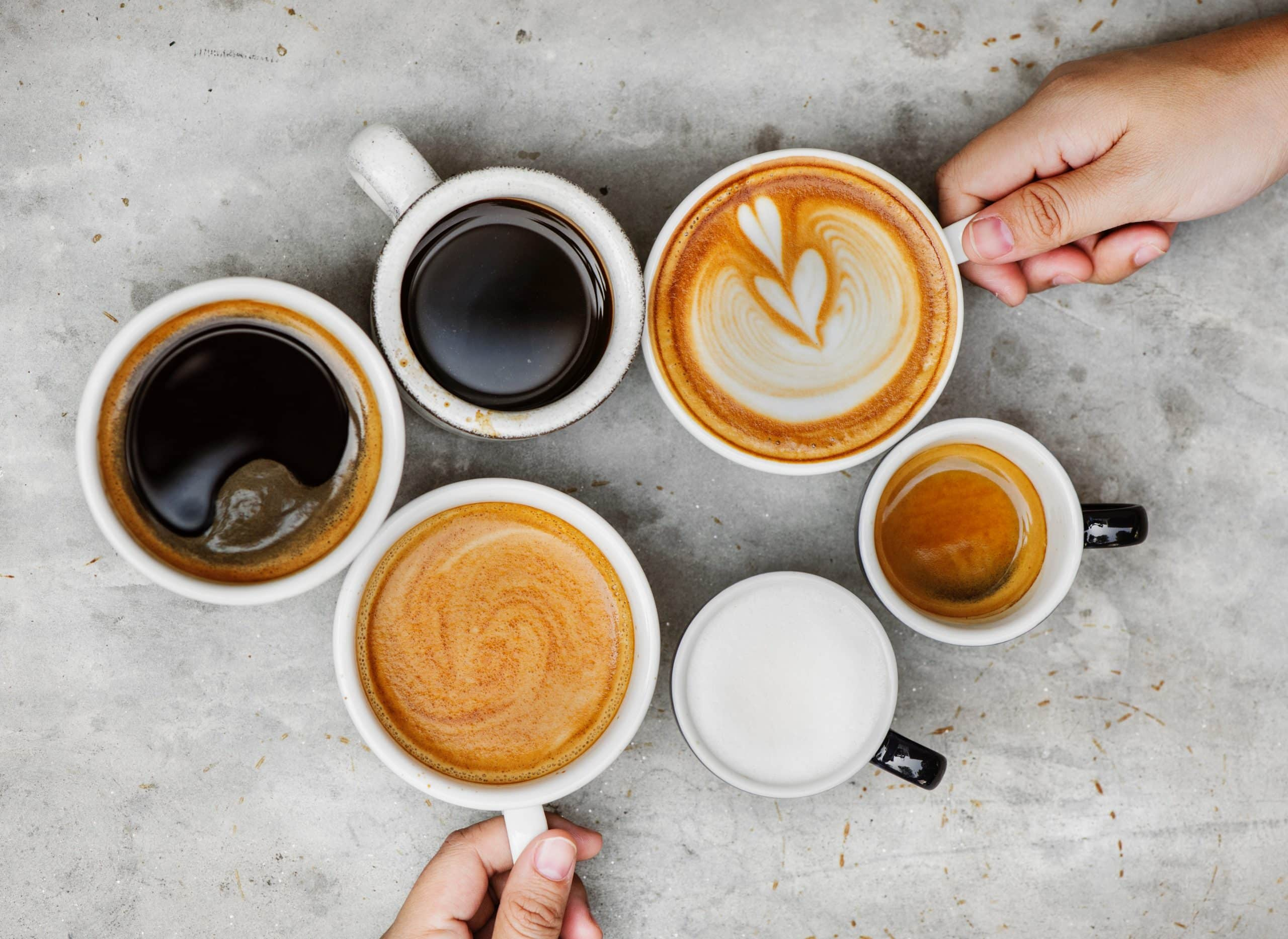 six cups of delicious coffee, espressos, teas, and lattes in white mugs