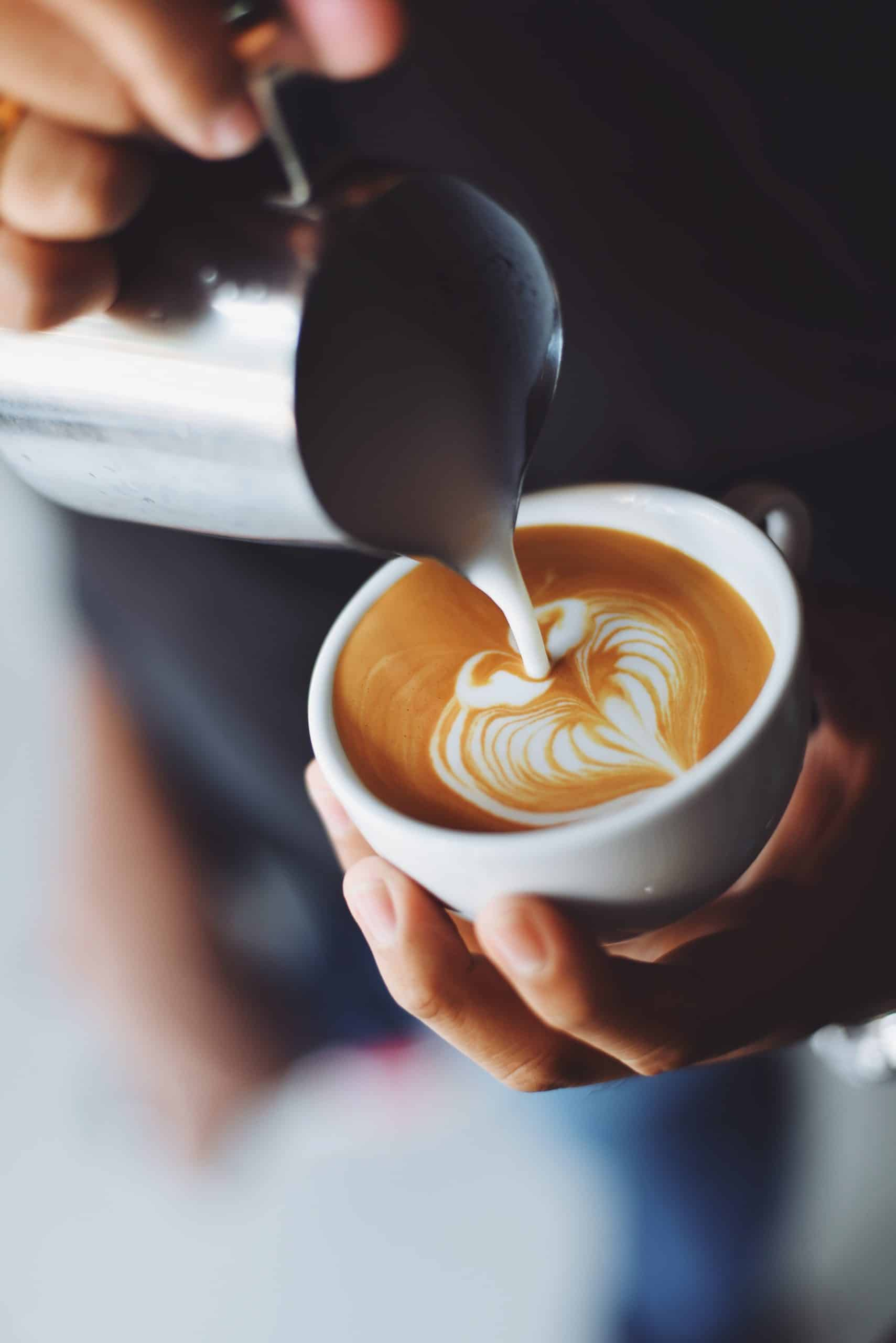 someone is pouring steamed milk into a latte while making a beautiful latte heart