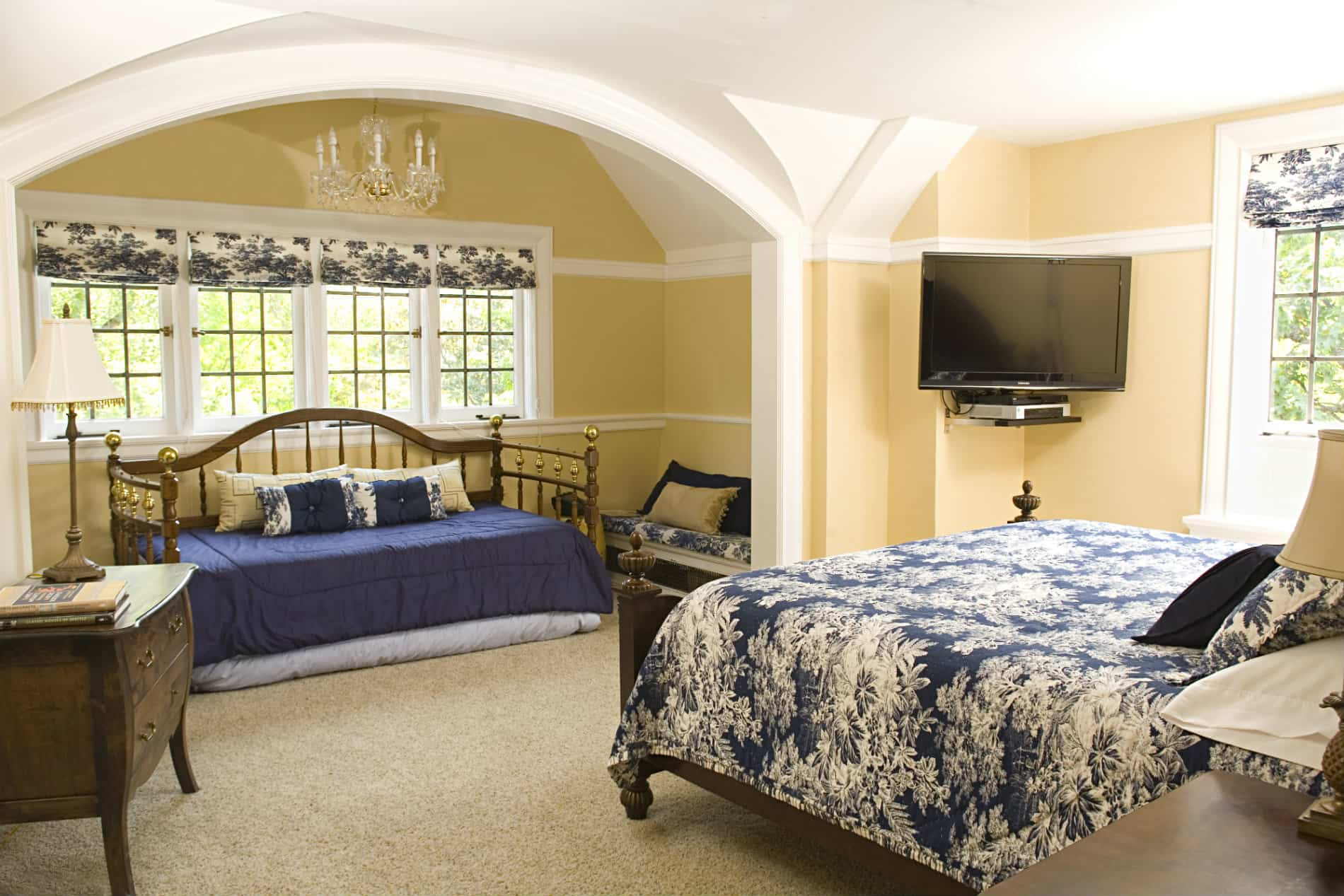 Twin size bed agaist a window looking at a queen size window with a blue comforter.