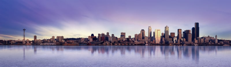 a panoramic view of Seattle over the still water under a blue and purple cloudy sky